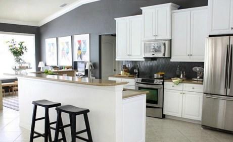 Το γκρι-ανθρακί χρώμα που χρησιμοποιήθηκε ανάμεσα στα ντουλάπια δημιούργησε μια πολύ ωραία αντίθεση με το λευκό των ντουλαπιών.