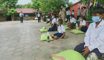 Students sit with their food donations