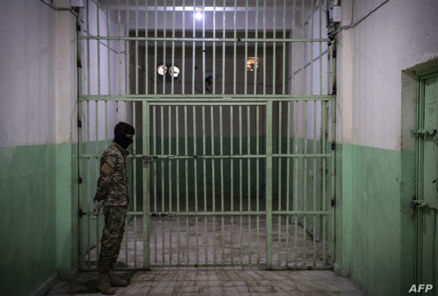 A member of the Syrian Democratic Forces (SDF) stands guard in a prison where men suspected to be afiliated with the Islamic…
