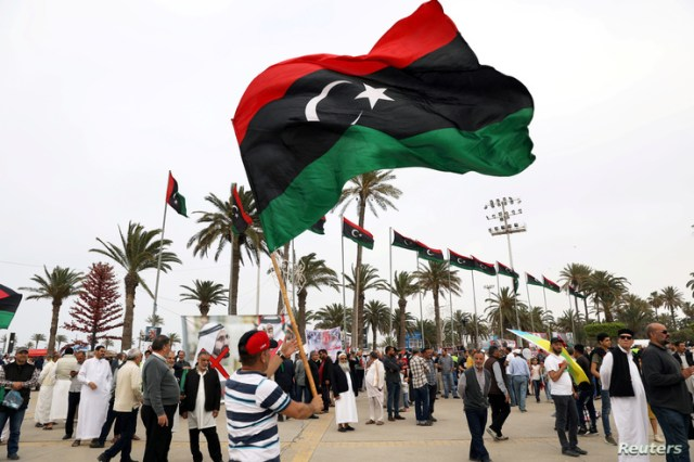 FILE PHOTO: A Libyan man waves a Libyan flag during a demonstration to demand an end to the Khalifa Haftar's offensive against…