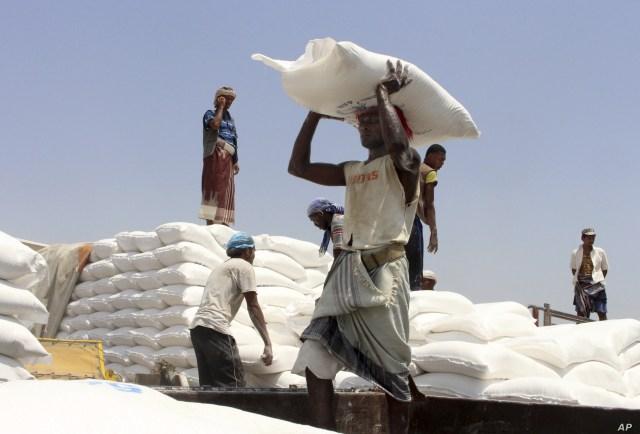 FILE - Men deliver U.N. World Food Program (WFP) aid in Aslam, Hajjah, Yemen, Sept. 21, 2018.