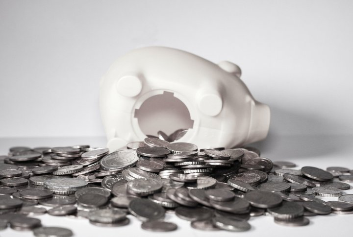 Piggy bank tipped over with coins spilling out