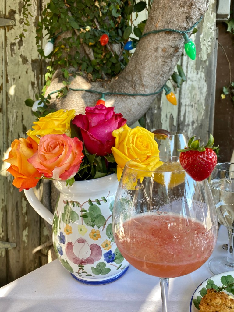 Hand painted pitcher with roses, strawberry mimosa, christmas lights, alfresco brunch