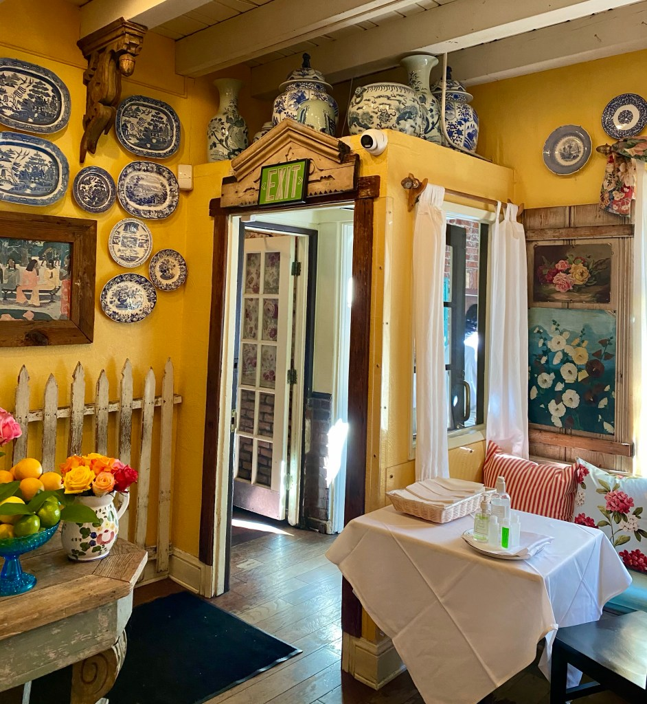 The Ivy, blue and white china, yellow walls, indoor picket fence
