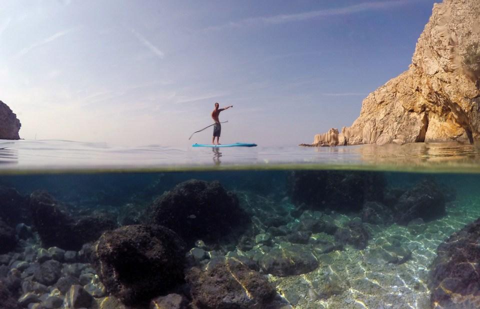Stand up paddler paddling over underwater landscapes split photo
