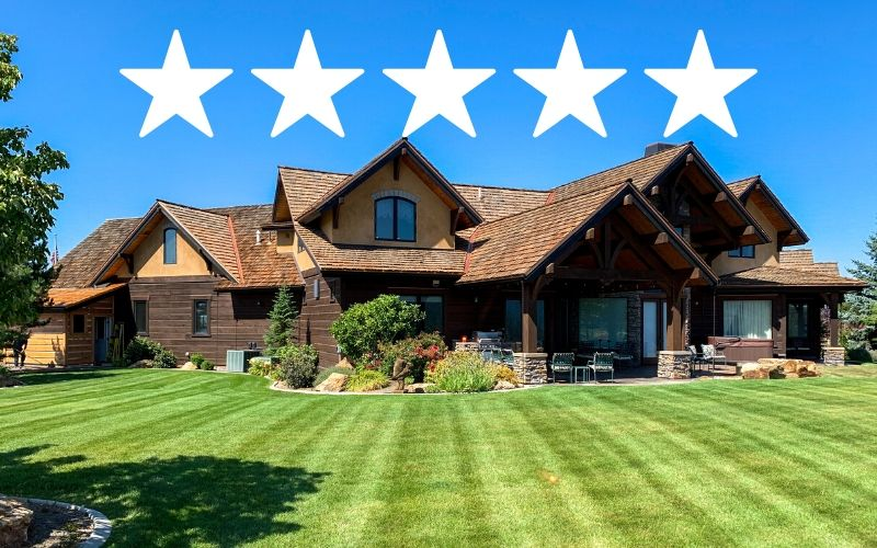 A Spokane home recently services by Spokane's Finest Lawns. The grass is freshly mowed. There's a 5 star graphic above the photo.