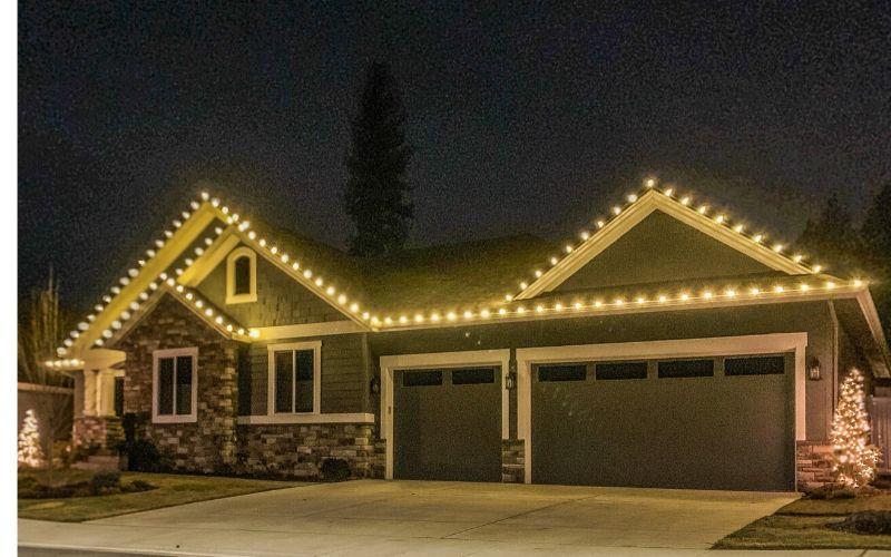 A single story home lined with warm Christmas lights.