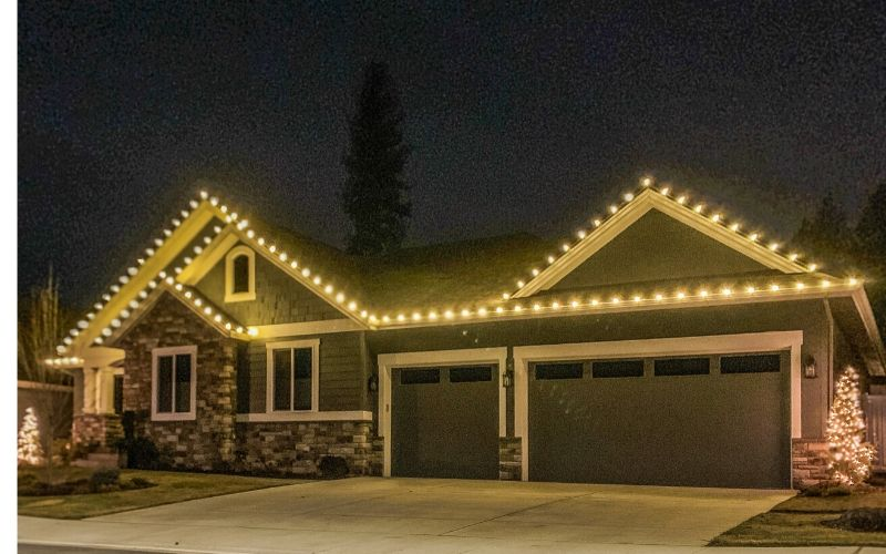 A single story home lined with warm Christmas lights.