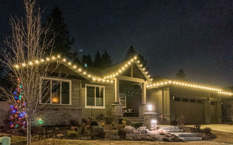 A single story Spokane home lined with warm, white Christmas lights.