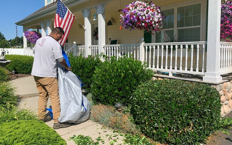 A Spokane's Finest Lawns employee gathering clippings for disposal after a landscape cleanup.
