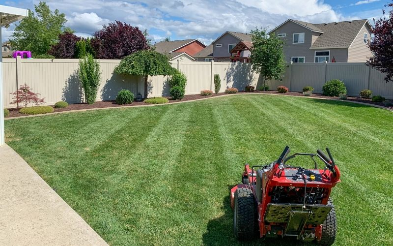 A large commercial lawn mower sitting in a back yard after a grass cutting service. There are visible mowing stripes in the grass.