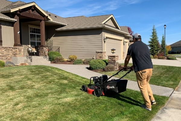 Lawn care employing push mowing a front lawn.