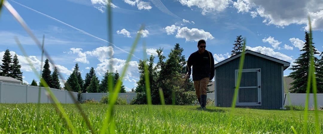 A Spokane's Finest Lawns employee preparing for a lawn fertilization treatment.