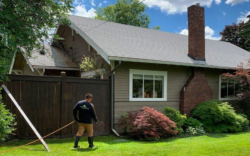 A Spokane's Finest Lawns employee applying fertilizer to a lawn.
