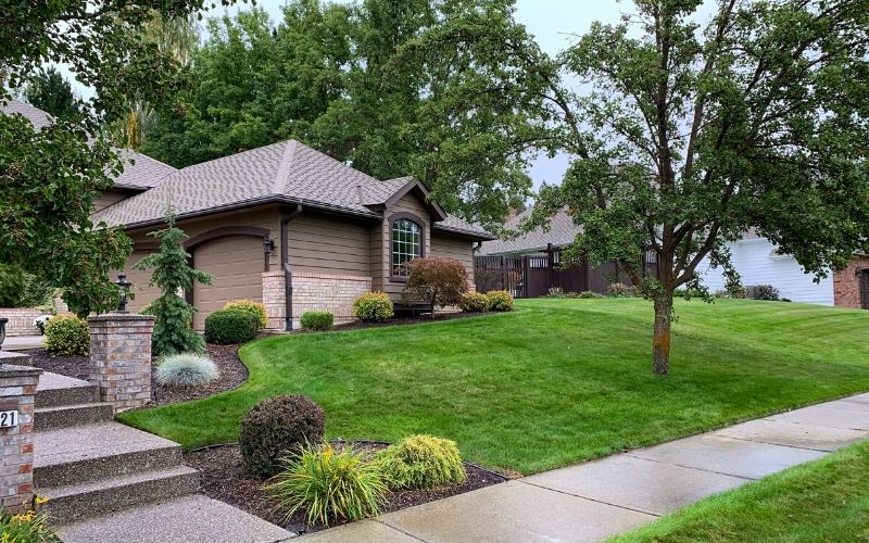 A beautiful Spokane home with a bright green and lush lawn on a fall day.