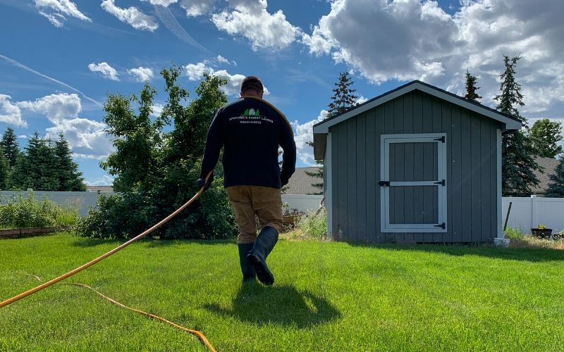 A Spokane's Finest Lawns employee performing a lawn fertilization treatment in a back yard.