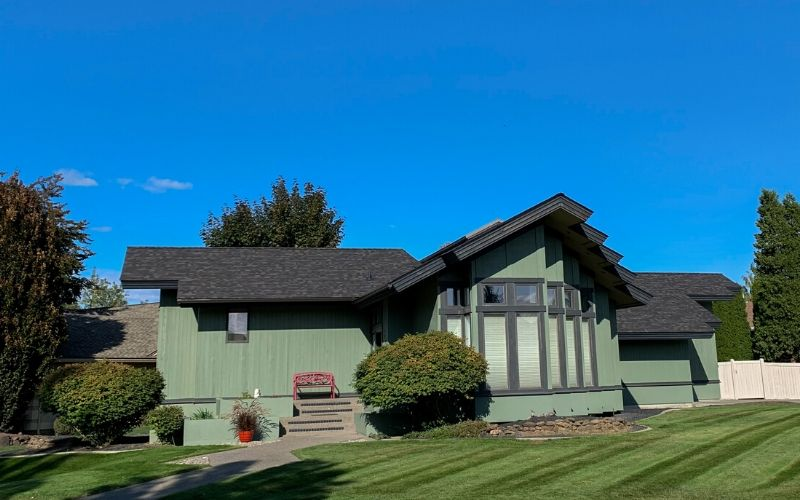 A residential Spokane home with a freshly mowed front lawn. There are visible mowing stripes in the grass.