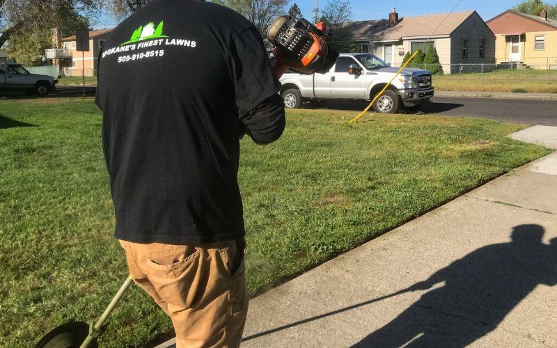 A Spokane's Finest Lawns employee edging a sidewalk.