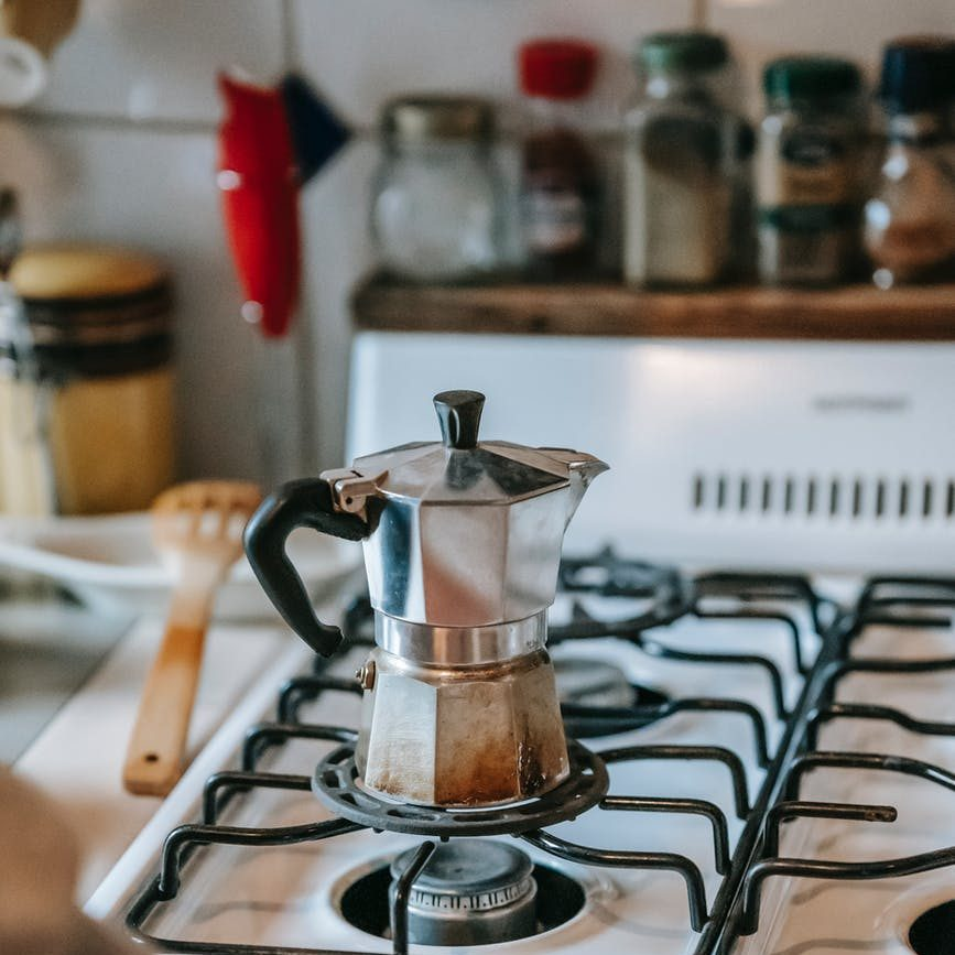 anonymous lady brewing coffee in geyser pot in kitchen