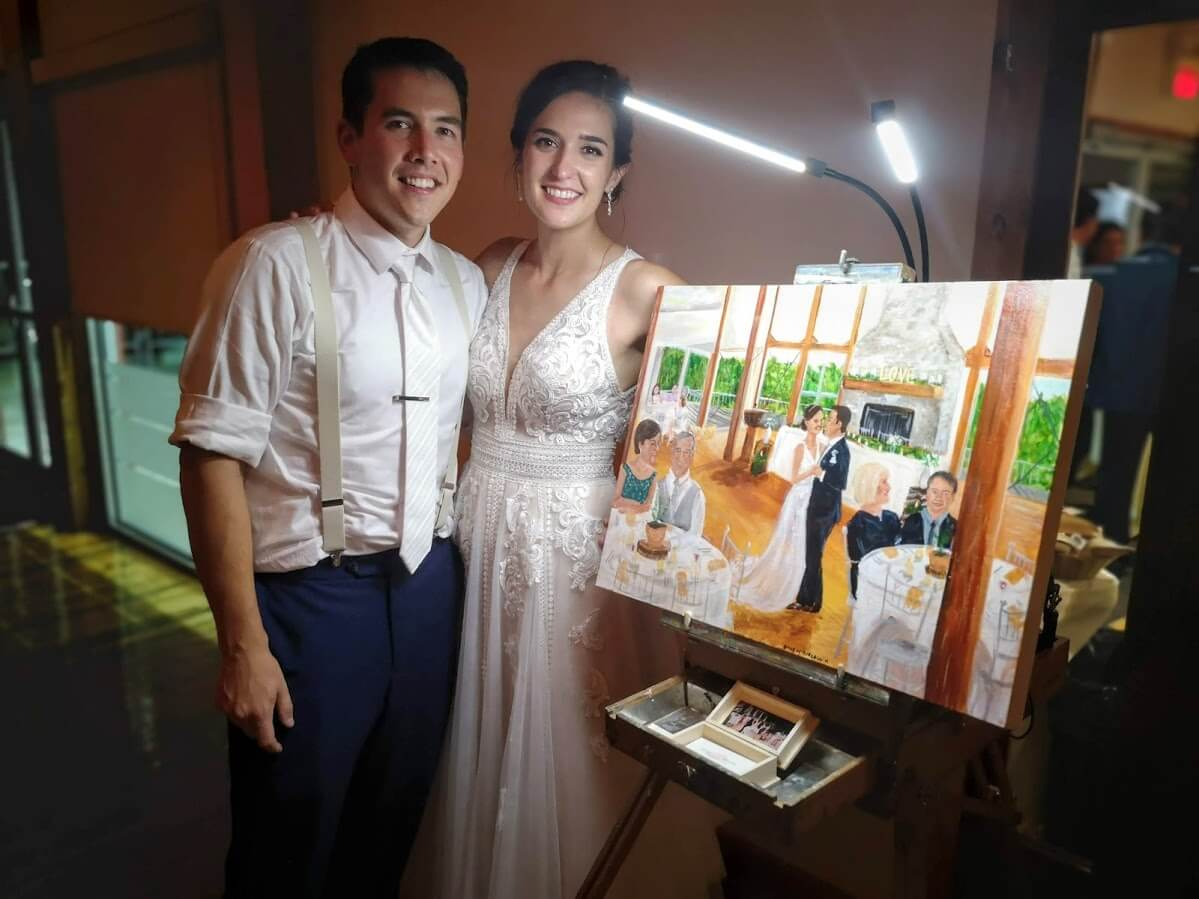 Newlyweds pose with a painting of their first dance by Emily McDougall.