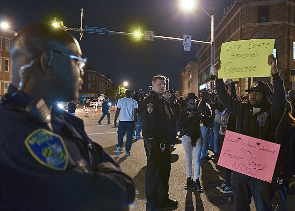 Protesters call for justice for Freddie Gray as Baltimore police officers watch.