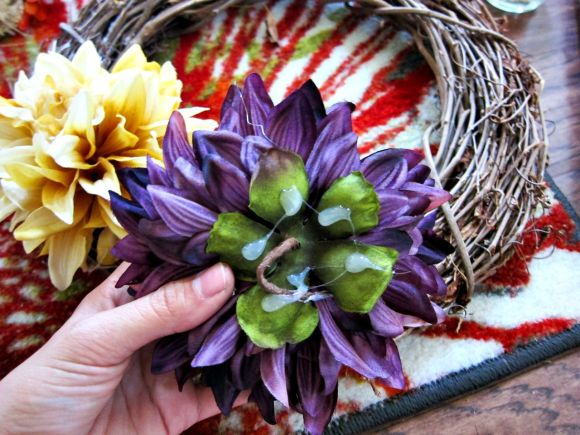 Hot glueing fake flowers to a wreath