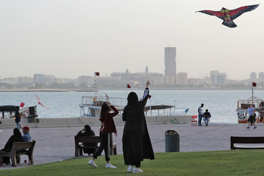 A girl and a woman fly a kite along the promenade by the Doha corniche in the Qatari capital on March 16, 2020.