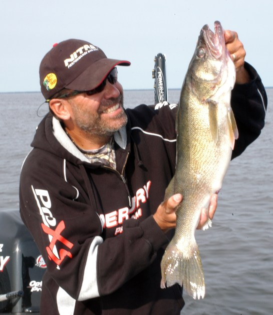 """Keith Kavajecz with a walleye:  It used to be thought that the springtime """"skinny water"""" crankbait trolling pattern was only prevalent on lakes in the southern reaches of the walleye belt. However, a resourceful number of walleye fishermen have opened a lot of minds to what the skinny water can produce in spring."""