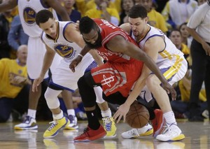 Houston Rockets guard James Harden, center, loses the ball on the game's final play as he Golden State Warriors guards Stephen Curry, left, and Klay Thompson defend during the second half of Game 2 of the NBA basketball Western Conference finals in Oakland, Calif., Thursday, May 21, 2015. The Warriors won 99-98. AP PHOTO.