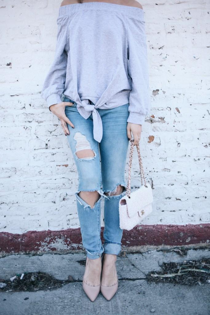 Blogger Mary Krosnjar wearing distressed Blank NYC denim and Ily Off the Shoulder Tie Sweatshirt