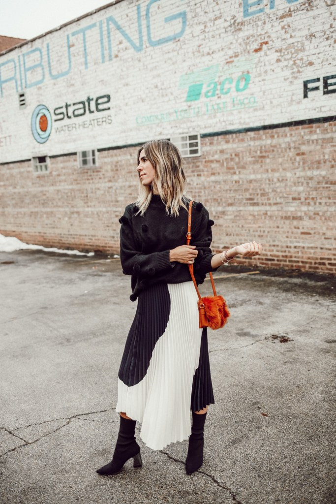 Blogger Mary Krosnjar wearing Rachel Parcell Black Pom Pom Sweater and H&M pleated skirt