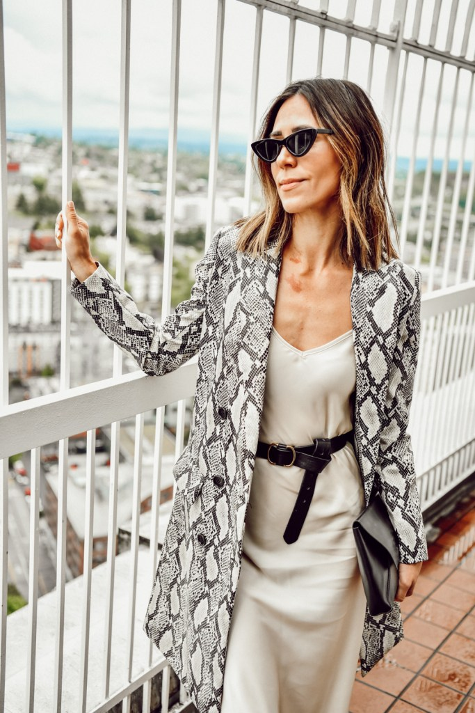Seattle Fashion Blogger Sportsanista wearing a cream slip dress with a black belt and faux leather snakeskin coat