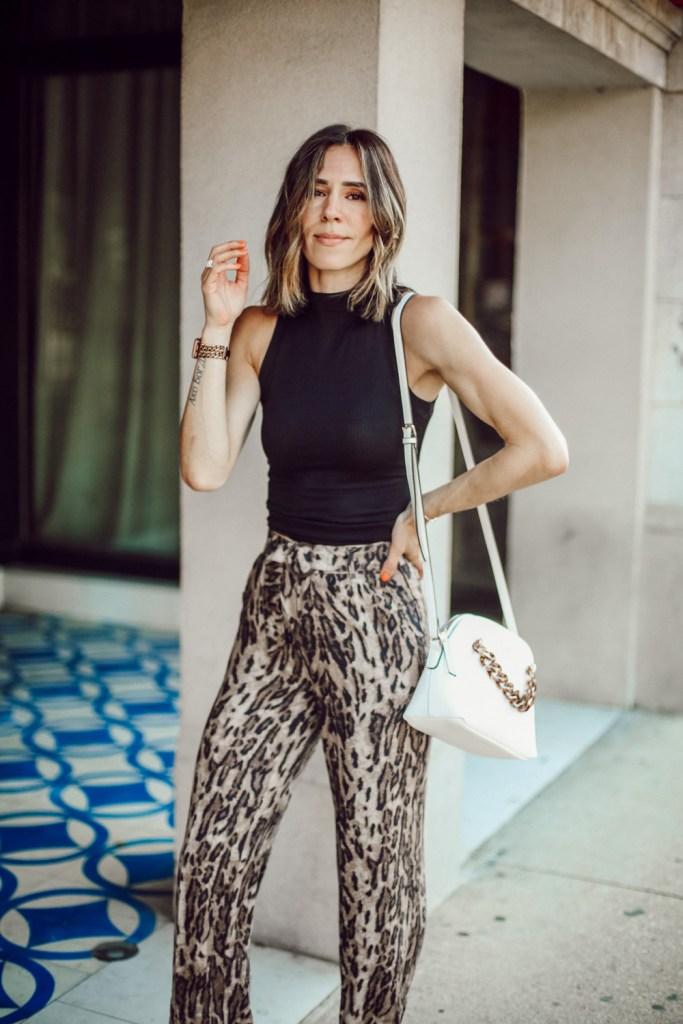 Fashion Blogger Sportsanista wearing black mock neck turtleneck and leopard wide leg pants for work