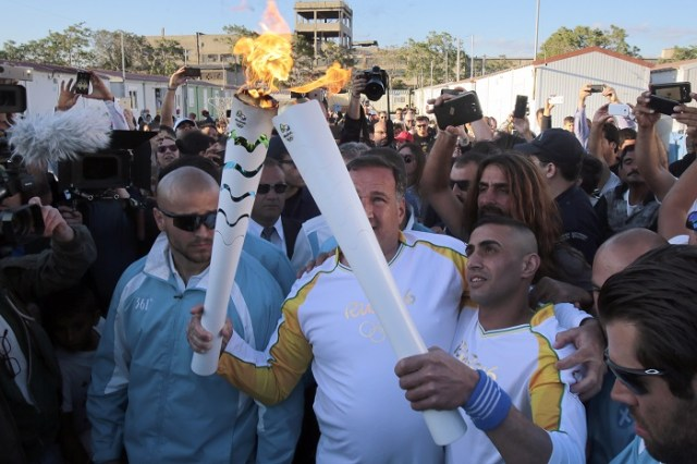 ATHENS, GREECE - APRIL 26: Syrian refugee athlete Ibrahim Al-Hussein (R) receives the Olympic flame from the head of Greece's Olympic Committee, Spyros Capralos, at the Elaionas camp that is home to about 1,500 refugees and other migrants on April 26, 2016 in Athens, Greece. (Photo by Milos Bicanski/Getty Images)