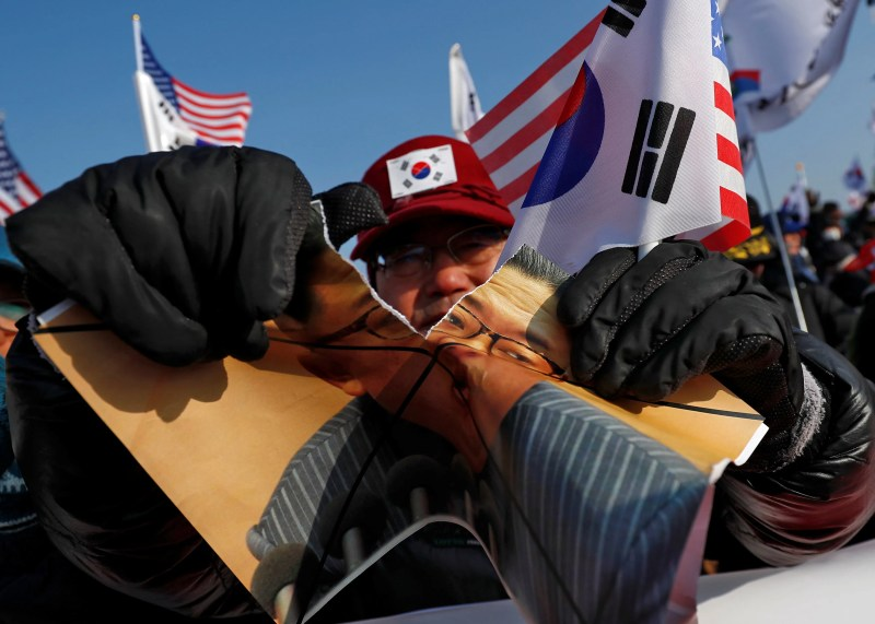 Protester tearing picture