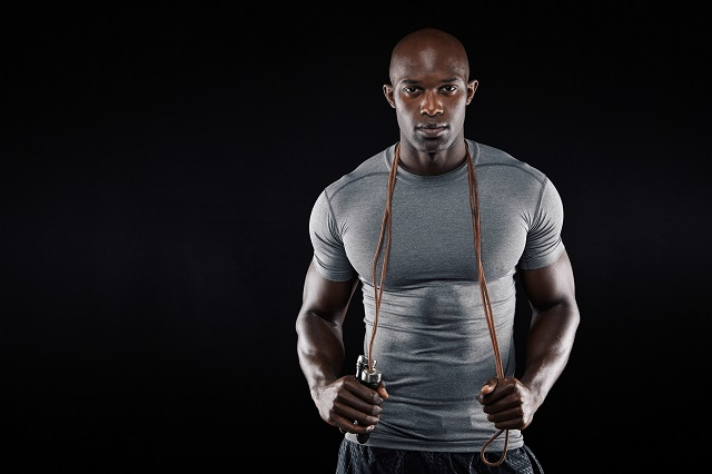 Handsome muscular man posing with jumping rope