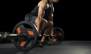 A man is weightlifting and bodybuilding with a heavy barbell