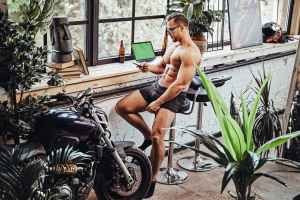 Strong man going through the process to buy SARMs online in office with bike and plants