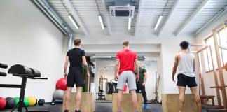 Men in gym with trainer exercising on fit boxes.