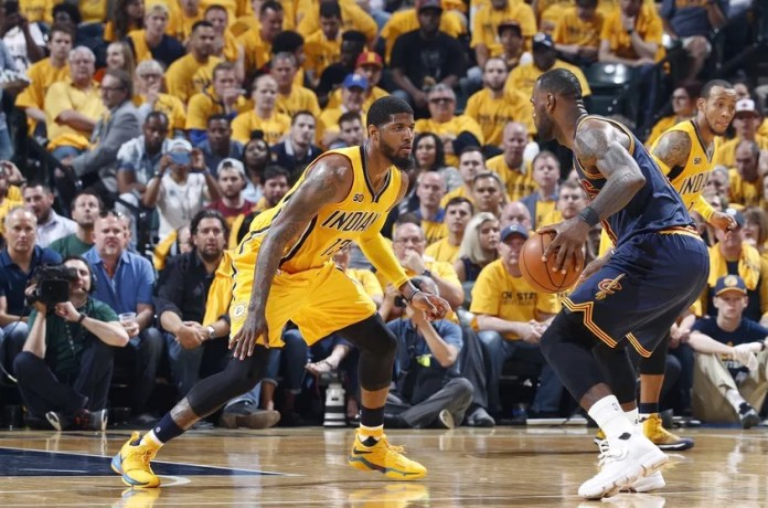 George tries to block LeBron James from dribbling pass him
