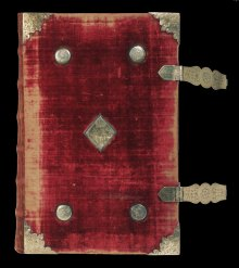 """The """"Bishop's Bible"""", 1568. The Folger owns the actual copy of the Bishops' Bible given to Queen Elizabeth by Matthew Parker, Archbishop of Canterbury in October 1568. Bound in red velvet, with silver-gilt bosses decorated Tudor roses, the Bible would have been used in her chapel. On the title page is an engraving of a youthful Elizabeth with flowing hair. With Faith and Charity on each side, she becomes emblematic of Hope. Inside is a handcolored portrait of Sir Robert Dudley, her favorite."""