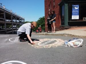 A street artist decorates one of the Enjoy Troy decals in the crosswalk at the intersection of State and River Streets in downtown Troy during River Fest on Saturday, June 18.