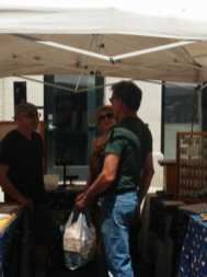 River Fest attendees converse with one of the many craft vendors on hand for the event.