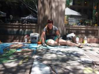 A sidewalk chalk artist works on her entry in the annual contest outside the Arts Center of the Capital Region during Troy River Fest on Saturday, June 18.