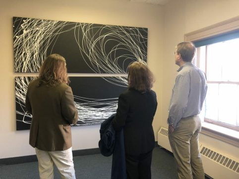Bethlehem Supervisor David VanLuven and his wife listen to Nighswonger talk about this pair of paintings on the 2nd floor of 343 Delaware Avenue.
