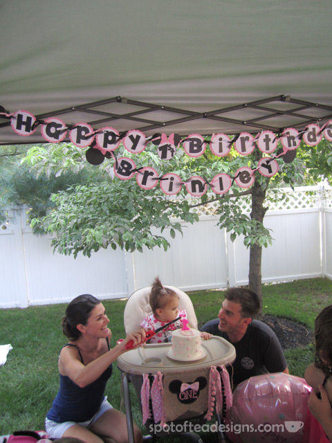 Minnie Mouse First Birthday Party: Banner overhead and on high chair for cake | spotofteadesigns.com