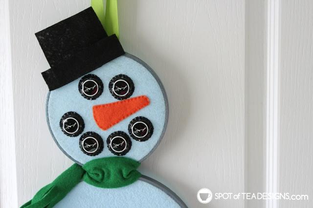 Mixed media snowman wall art - turn embroidery hoops, felt and bottle caps into winter wall art! | spotofteadesigns.com