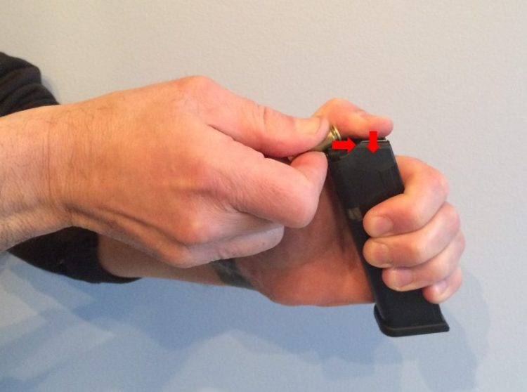 Use your strong hand and begin to insert a cartridge into the magazine while simultaneously pushing down on the spring with your thumb of the weak hand.