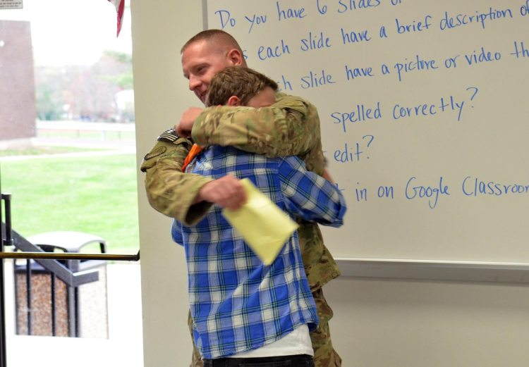 Pennsylvania Air National Guardsman Kevin Curcio pulls his son Bennett into a hug during a surprise visit to his seventh grade Social Studies classroom at Indian Crest Junior High School. Curcio just got back from a deployment to Afghanistan and has not seen his son since March. Wednesday, November 5, 2014. Photo by Geoff Patton