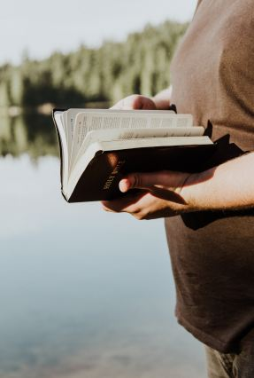 Person reading the bible while standing b a lake.